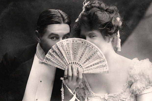 Photo of a couple holding up a fan