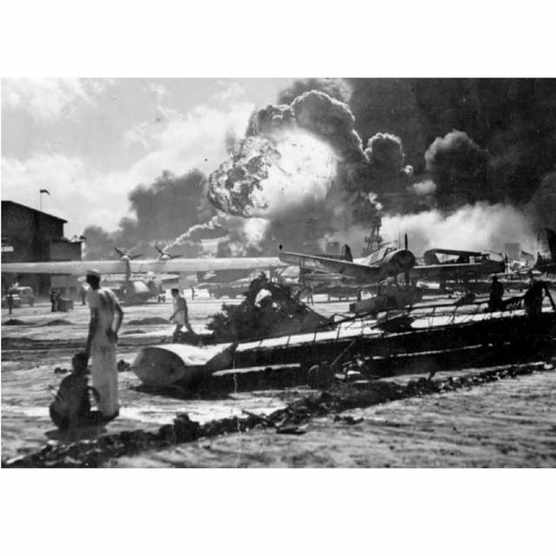 The Pearl Harbour attack, 7 December 1941: sailors at the Naval Air Station, Ford Island, stand amid wreckage watching as the USS Shaw explodes in the centre background. The USS Nevada is also visible in the middle background, with her bow headed toward the left. (Photo by Fox Photos/Getty Images)