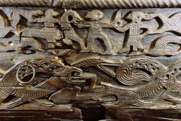 A detail of the decorative carving on the side of the Oseberg cart c850 AD. A woman with streaming hair apparently restrains a man's sword arm as he strikes at a horseman accompanied by a dog. Below is a frieze of intertwined serpentine beasts. (Photo by Werner Forman/Universal Images Group/Getty Images)