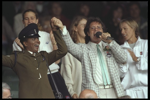 Sir Cliff Richard entertains the crowds as rain delays the matches at the 1996 Championships (Clive Brunskill/Allsport UK/Getty Images)