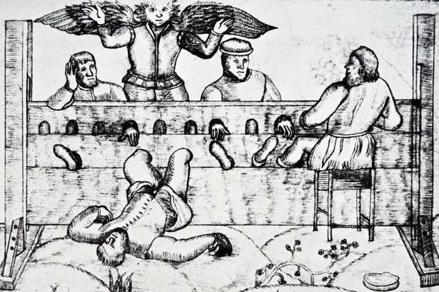 A woodcut print depicting the stocks, a form of Elizabethan punishment. Dated 16th century. (Photo by: Universal History Archive/UIG via Getty Images)