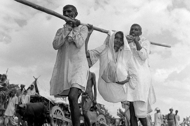 Two men carrying old woman as they migrate, following the Partition of India in 1947