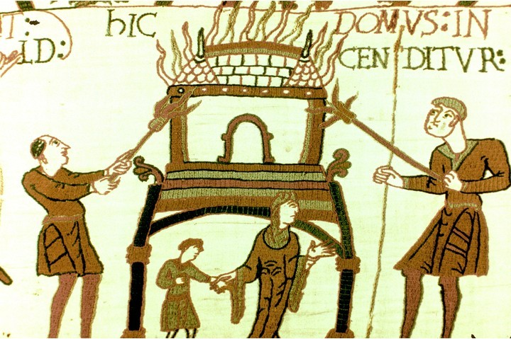 Section of the Bayeux Tapestry depicting a woman and child fleeing from a burning house. (Photo by Universal History Archive/Getty Images)