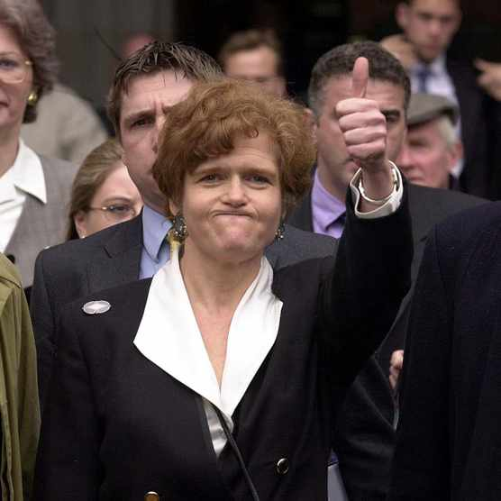 US academic Deborah Lipstadt exults the High Court in London after winning a libel case brought against her by British historian David Irving, 11 April 2000. (Photo by Martyn Hayhow/AFP/Getty Images)