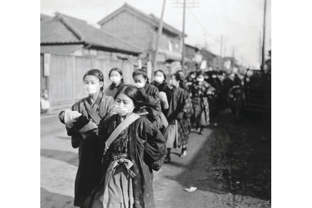 Schoolgirls in Tokyo don protective face masks to guard against flu transmission during the outbreak. The use of such masks by the Japanese public boomed during the 1918–20 epidemic and subsequent disease outbreaks, and remains common in Japan today. (Getty images)