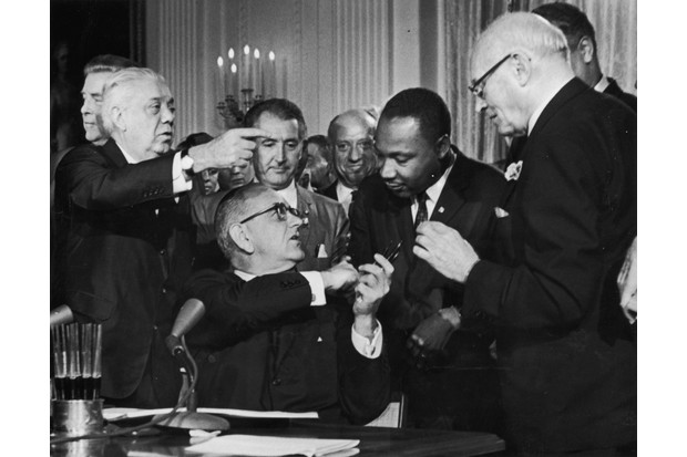 President Lyndon Johnson accepts a handshake from Dr Martin Luther King at the signing of the Civil Rights Act in 1964, legislation that JFK was unable to make law. (Photo by Hulton Archive/Getty Images)