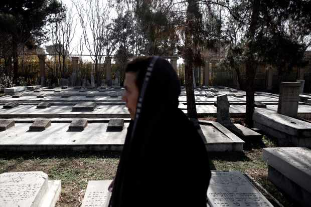 An Iranian Jewish woman walks past the graves of Polish Jews who died in Iran during and after the Second World War