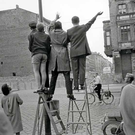 West Berlin inhabitants wave at the newly erected Berlin Wall, 1961. (Photo by Imagno/Getty Images)