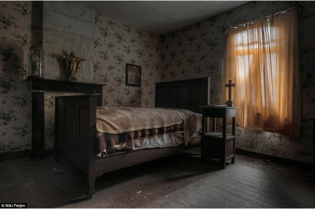 Photo of a deserted bedroom with single bed and Christian iconography