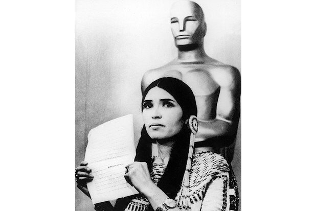 Sacheen Littlefeather holds a written statement from actor Marlon Brando refusing his Best Actor award, on stage at the Academy Awards, 1973. (Hulton Archive/Getty Images)