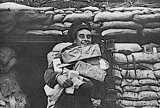Front cover photograph from The Sphere, December 1916 showing a joyful soldier in a trench laden with Christmas parcels.     Date: 30th December 1916