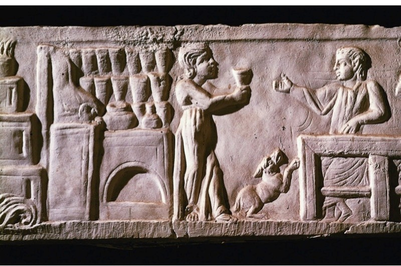 The patrons of a tavern enjoy a drink in this second-century AD relief. (© Getty)