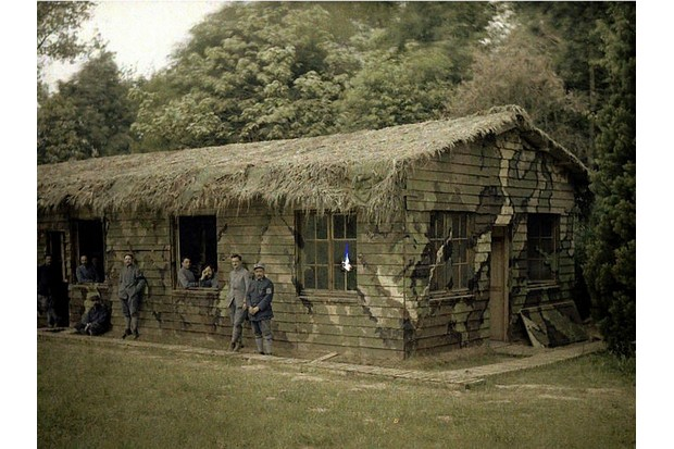 Nine French soldiers at a wooden building with military camouflage. 1917. Color photo (Autochrome Lumière) by Fernand Cuville (1887-1927). World War I, Western Front. Soissons, Aisne, France. (Photo by Galerie Bilderwelt/Getty Images)