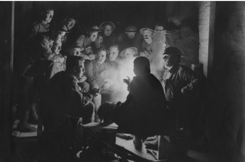 c1916: British soldiers sitting around a lamp in their trench. (Photo by Hulton Archive/Getty Images)