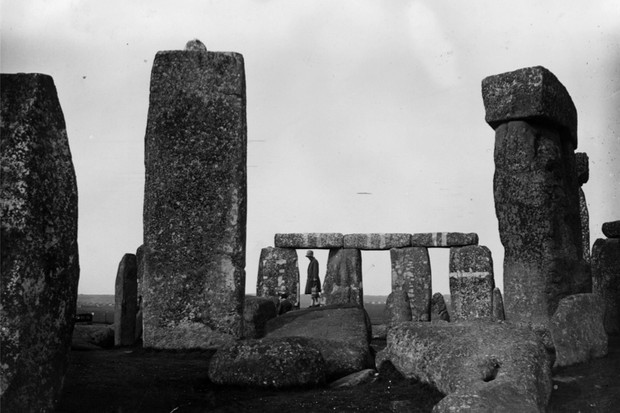 f5264db72b853 A visitor stands on a toppled standing stone at the megalithic structure of  Stonehenge on Salisbury