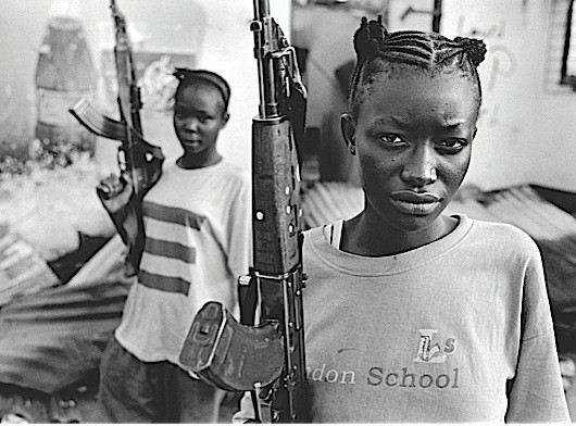 © Teun Voeten, Ganta, Liberia, June 23rd 2003.  Ganta is a small town, 250kilometers NE of Monrovia, on the border with Guinnée.  Rebels from the LURD (Liberians United for Reconciliation and Democracy) captured the town but were beaten back by President Taylor's goverment forces.  During fierce fighting, the LURD rebels, who have their bases in Guinnée, relentlessly shelled the town.  Female members of government armed forces/militias standing on guard.