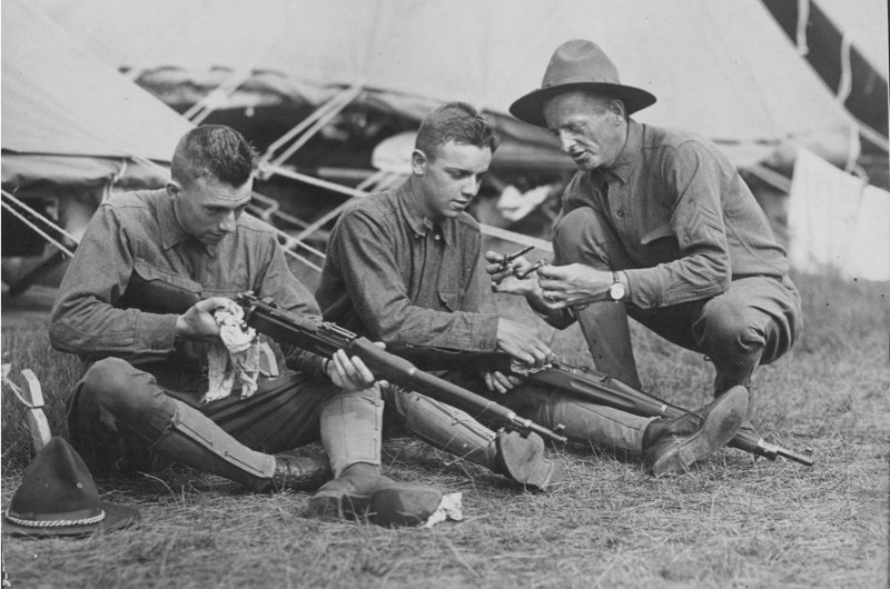 A US soldier teaching two junior 'rookie' recruits how to clean a gun during the First World War