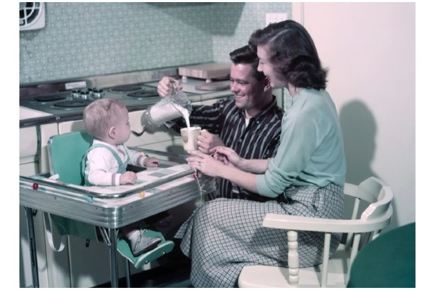 A Young Couple From The 1950s Pouring Milk For Baby Sat In Popular Formica