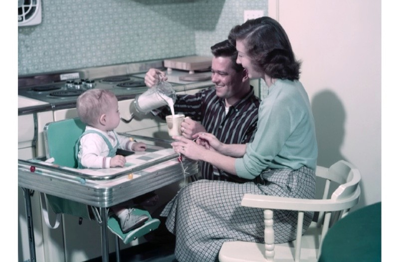 A young couple from the 1950s pouring milk for a baby sat in a popular Formica-branded baby chair. (H. Armstrong Roberts/ClassicStock/Getty Images)