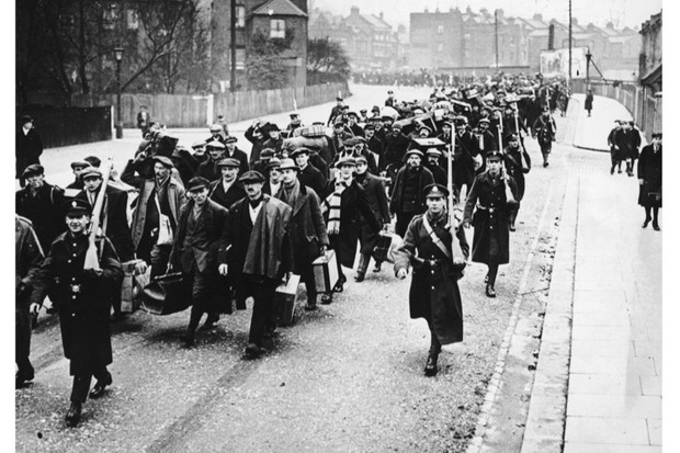 New recruits march alongside armed officers following the outbreak of the First World War. (Hulton Archive/Getty Images)