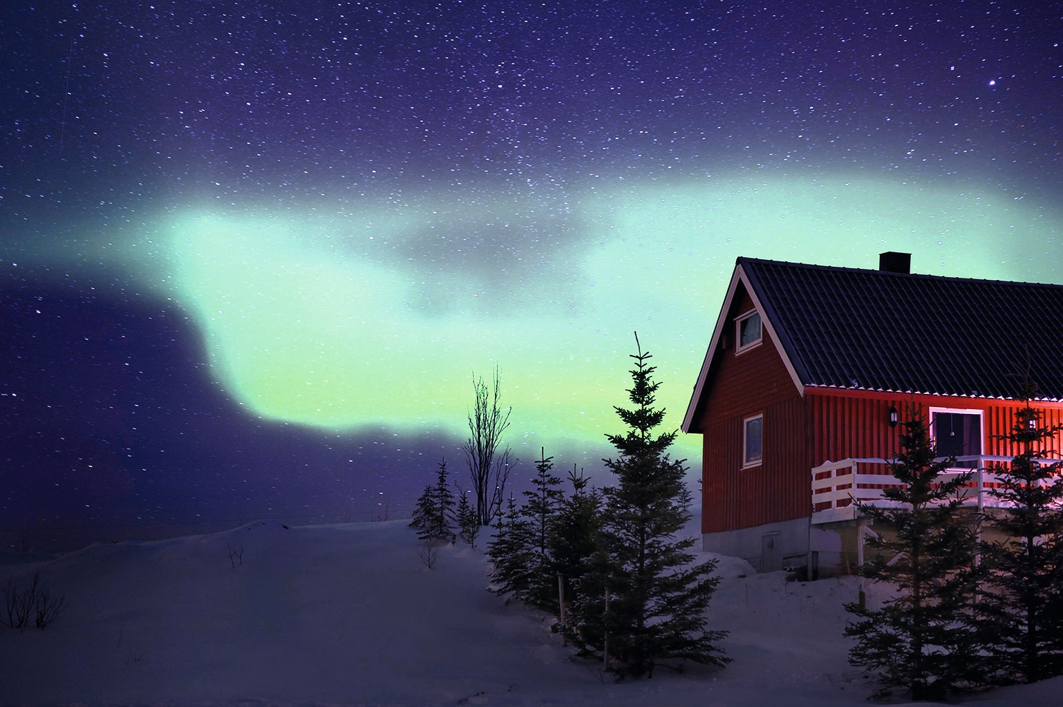 Red Norwegian house with an aurora in winter, Tromso Northern Norway, Norway