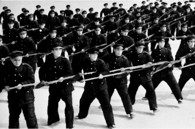 Nationalist militia armed with sharpened bamboo spears go through drill on a parade in the city of Tsian in April 1948