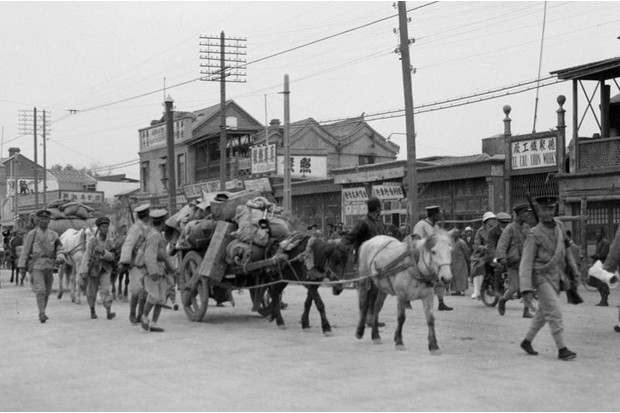 The baggage train of a warlord army enters a Chinese captured town, 1920s