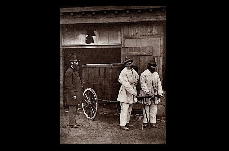 Photograph of two men pulling a mobile disinfection unit.