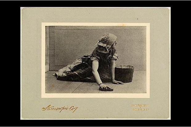 A 19th century maid scrubbing a floor.