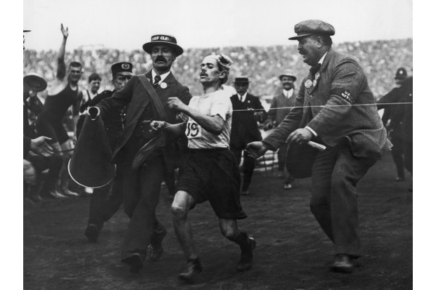 Dorando Pietri being helped over the line by a British official at the 1908 London Olympics. (Photo by Hulton Archive/Getty Images)