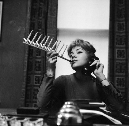 Model Frances Richards smokes a pack of cigarettes all on one cigarette holder, c1955. (Credit: Jacobsen/Getty Images)