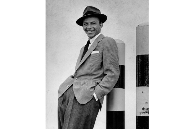 Popular American entertainer Frank Sinatra (1915 - 1998), in a hat, sport coat, and tie, smiles as he leans against a bollard on the 20th Century Fox studio lot, California, April 1954. (Photo by Sharland/Time & Life Pictures/Getty Images)
