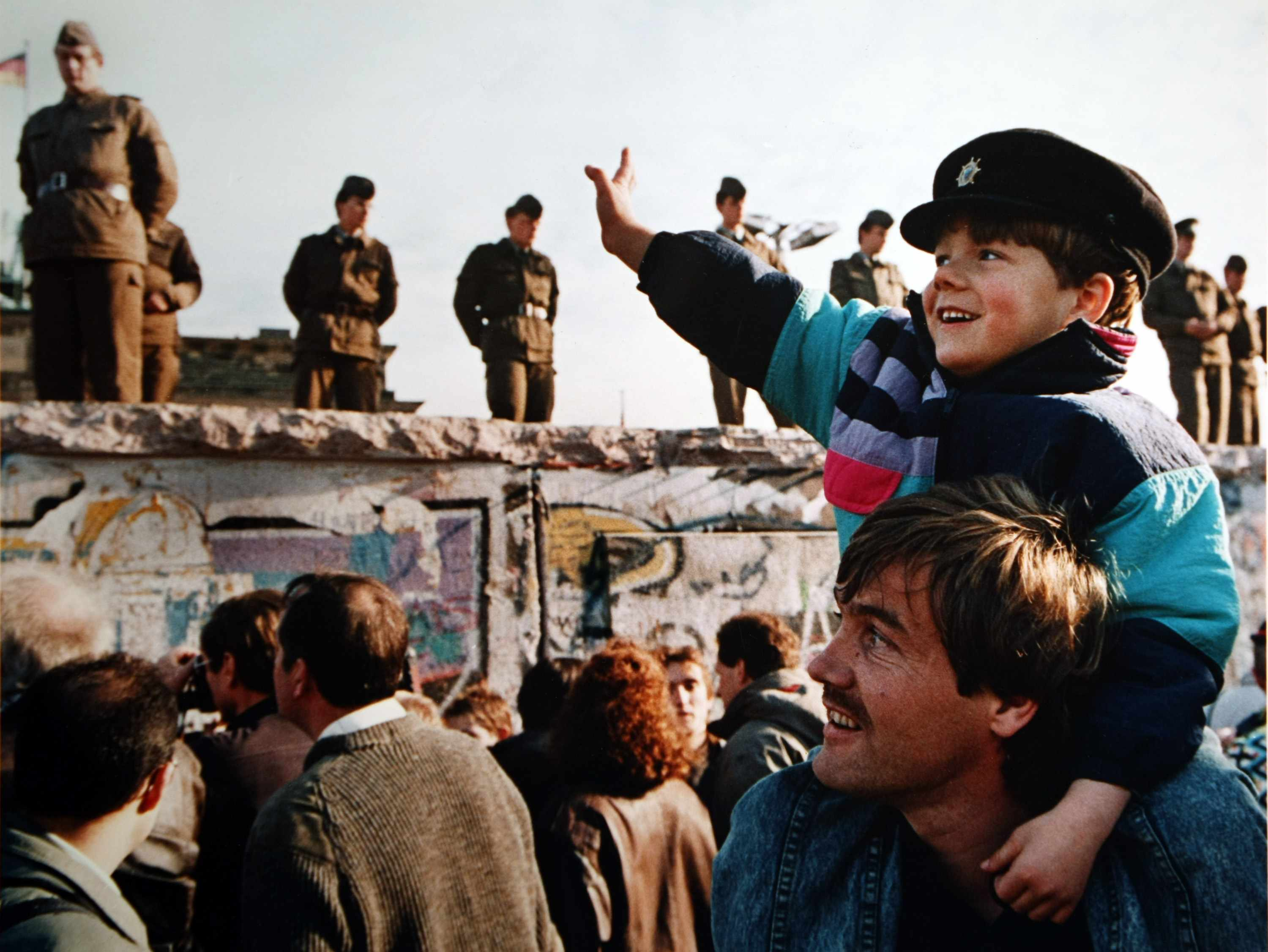 Boy Waves To Soldiers On The Berlin Wall