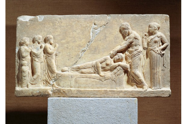 A marble relief depicting either Ascelpius, the god of medicine, or Hippocrates, a physician in Ancient Greece, treating an unwell woman. (De Agostini/Getty Images)