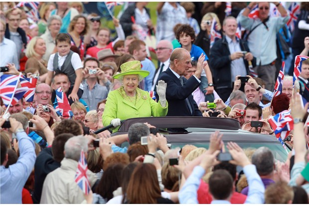 The Queen and Prince Phillip, Duke of Edinburgh, drive in a open top car as they attended a special diamond jubilee event in Belfast, Northern Ireland, in 2012. (Photo by Peter Muhly/AFP/Getty Images)