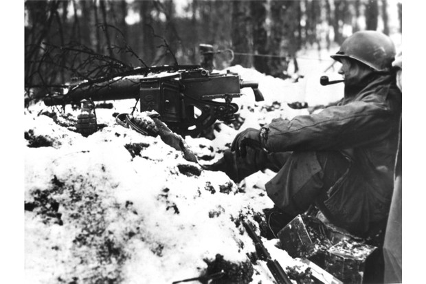 An American infantryman take time out for a pipe smoke during a lull in the fighting during the Battle of the Bulge (January 1945). (Photo by Photo12/UIG/Getty Images)
