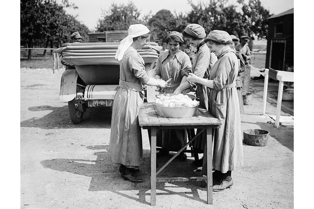 Cooks of the WAAC prepare vegetables at an infantry camp in Rouen, France, 24 July 1917. (Photo by Lt. J W Brooke/ IWM via Getty Images)