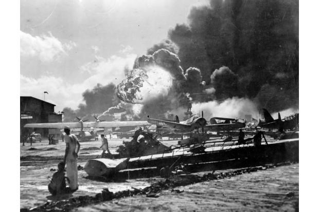 Pearl Harbor: sailors stand amid wreckage watching as the USS Shaw explodes in the centre background. (Photo by Fox Photos/Getty Images)