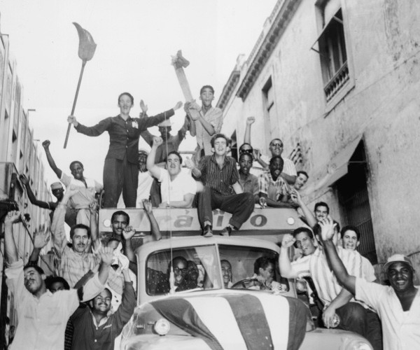 A truck filled with Cuban men rides through a narrow Havana street in 1959