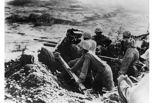 A marine gun crew fire on Japanese pillboxes on Okinawa. (Photo by Keystone/Getty Images)