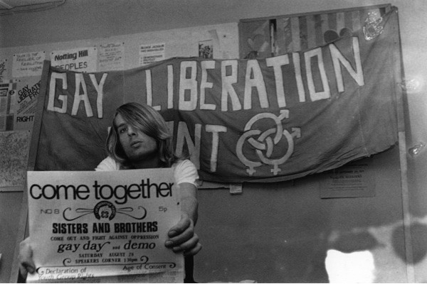 A member of the Gay Liberation Front holding a poster in around 1971. (Getty Images)