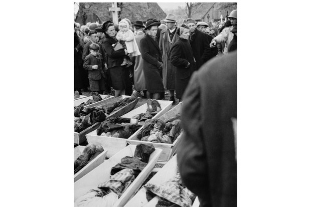 (Original Caption) German civilians file past the open coffins containing the bodies of 161 Polish Jews, shot by SS Troops in the woods outside Nuerenburg, as the bodies await burial in the town's Catholic cemetery. One woman is being forced to look by wordless command from American soldier, (R). Note the expressions on small children's faces. The civilians were forced to serve as pallbearers in the one mile march from the woods to the cemetery.