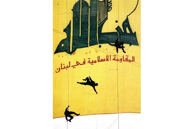 """BEIRUT, LEBANON - JANUARY 15: Black-clad Hezbollah militants descend in front of a giant banner reading """"Hezbollah, the Islamic Resistance in Lebanon,"""" 15 January in a southern suburb of Beirut to mark """"International Qods (Jerusalem) Day,"""" which was first established by Iran after the 1979 Islamic Revolution to show solidarity with the Palestinians against Israel. The Iranian-backed Hezbollah movement spearheads the armed struggle to oust Israeli occupation forces from southern Lebanon. (Photo credit should read HAYTHAM MUSAWI/AFP/Getty Images)"""
