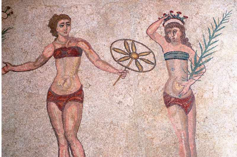 A mosaic that shows two Roman women exercising, one holds a flower and another holds a leaf