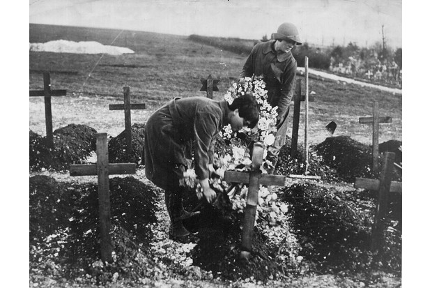 Gardeners of the Women's Army Auxiliary Corps placing wreaths on a grave in France. (Photo by: Robert Hunt Library/Windmill books/UIG via Getty images)