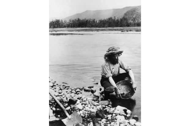 A gold prospector panning for alluvial gold in the Klondike, a region in the western region of the Yukon Territory, Canada, circa 1898. (Photo by Hulton Archive/Getty Images)