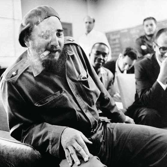 """In a cloud of smoke, a gloating Fidel Castro and his cigar meet the Press in June, 1961 after increasing the ransom for 1,173 prisoners captured by Cuban forces in the April Bay of Pigs invasion. An American """"Tractors for Freedom,"""" committee journeys to Havana to offer $2.5 million-worth of agricultural tractors for their release but Castro sends them away with a demand for $28 million worth. The prisoners are finally released in December, 1962, for $53 million in medical supplies. (Keystone-France/Gamma-Keystone/Getty Images)"""
