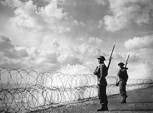 2nd September 1940:  Armed soldiers on guard on a south coast beach. Waves are breaking against a barbed wire barricade, signs of the strong winds which may have helped to hamper Hitler's plans for an invasion.  (Photo by Fox Photos/Getty Images)