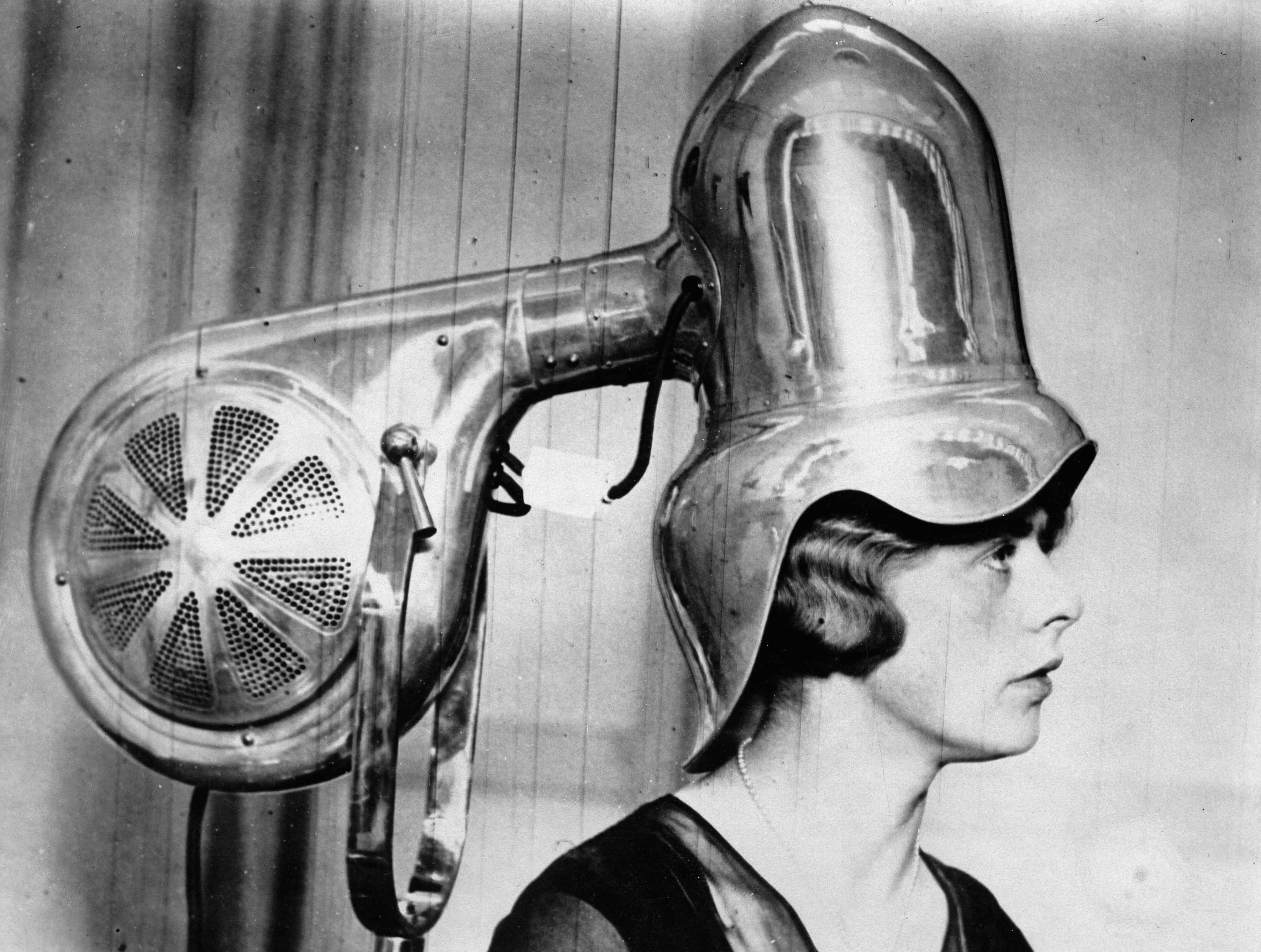 Woman using a large hairdryer in 1935