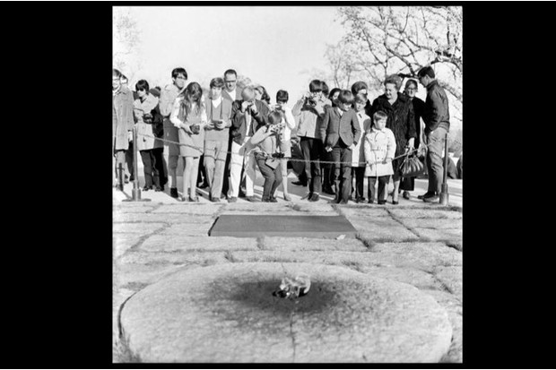 Tourists gather around the eternal flame at the resting place of JFK, at Arlington National Cemetery, March 1967